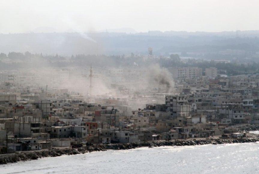 Virš apšaudomo Latakijos miesto sklinda dūmai.