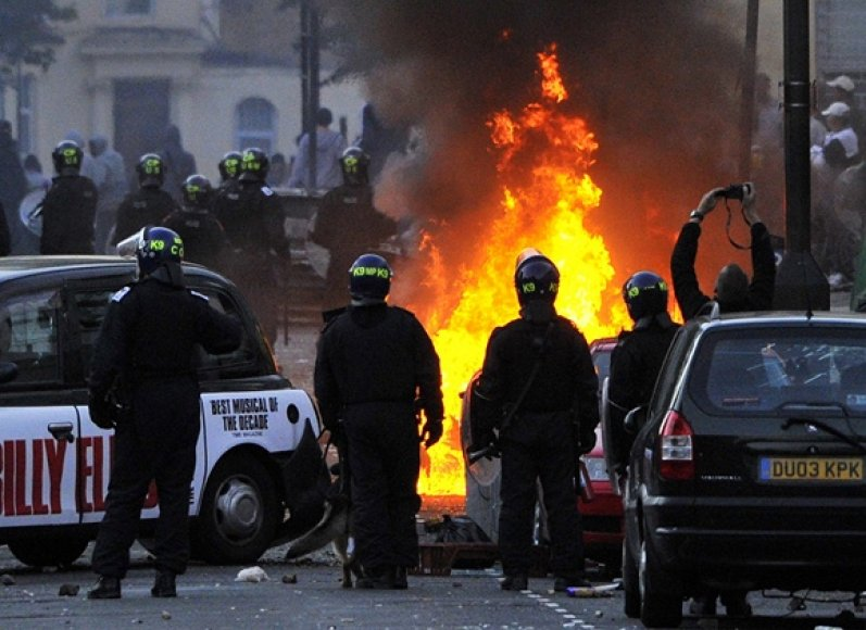 Policininkai stovi netoli degančio automobilio