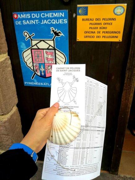 Monikos Svėrytės nuotr./Rankose – tik ką gautas piligrimo pasas, Jokūbo kriauklė ir albergų sąrašas, kelio reljefo žemėlapis