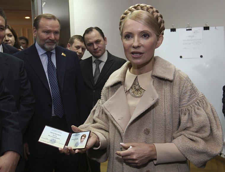 Julija Tymošenko demonstruoja kandidatės į prezidento postą pažymėjimą.