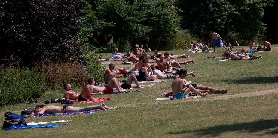 Pievoje žmonės mėgaujasi saulės voniomis.