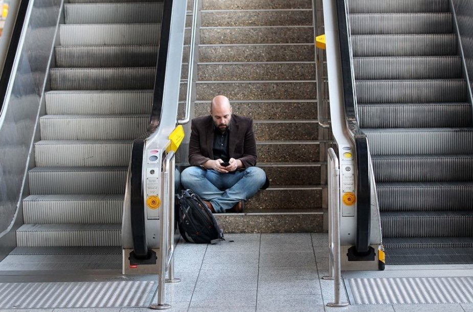 Vyras sėdi ant laiptų Frankfurto oro uoste.