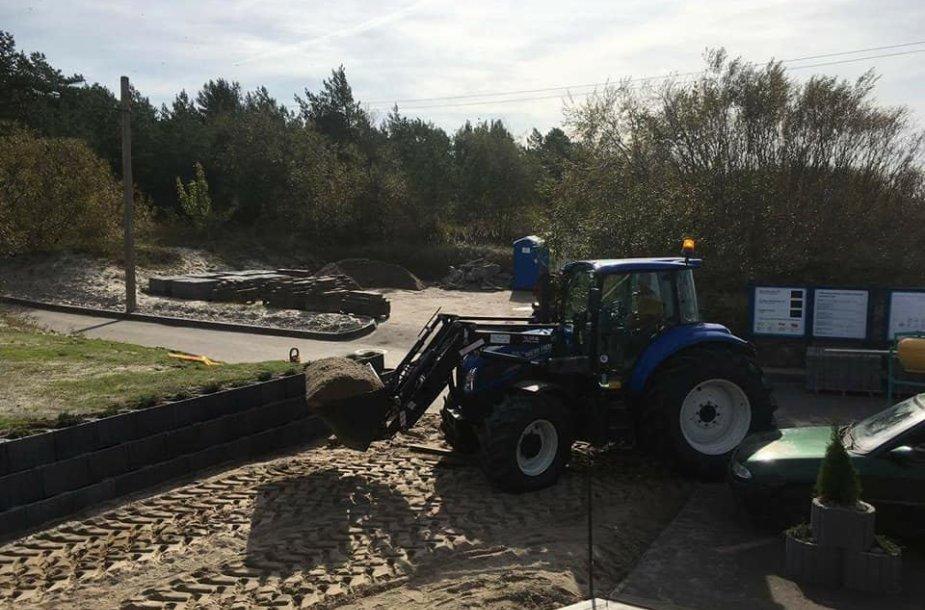 Traktorius vaduoja takus nuo užversto smėlio.