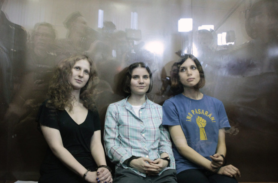 """Members of the female punk band """"Pussy Riot"""" (R-L) Nadezhda Tolokonnikova, Yekaterina Samutsevich and Maria Alyokhina sit in a glass-walled cage after a court hearing in Moscow, August 17, 2012. A judge sentenced three women who staged an anti-Kremlin protest on the altar of Moscow's main Russian Or"""
