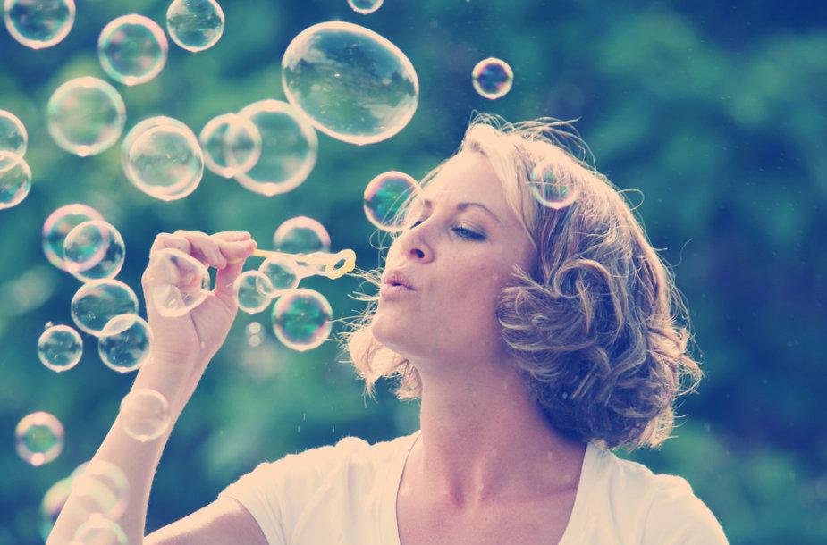 Moteris pučia muilo burbulus