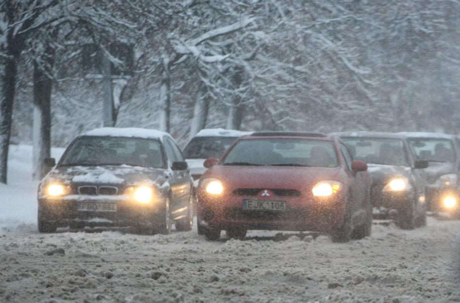 Automobiliai apsnigtoje gatvėje