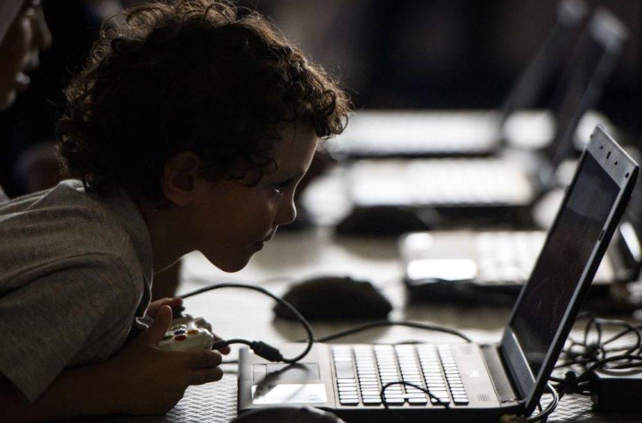 Vaikas žaidžia su kompiuteriu