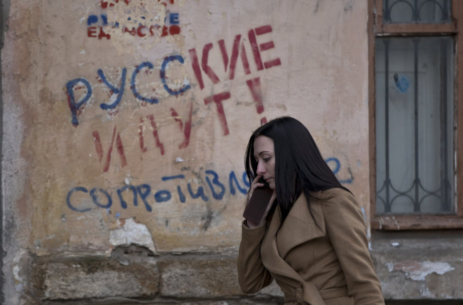 "FILE - In this Friday, March 7, 2014 file photo, a woman passes by a graffiti that reads ""The Russians are coming - Resistance"" in Simferopol, Ukraine. For the ethnic Ukrainians and Tatars who are the minority in the strategic peninsula, it is fear that dominates days before Crimea votes in a refere"