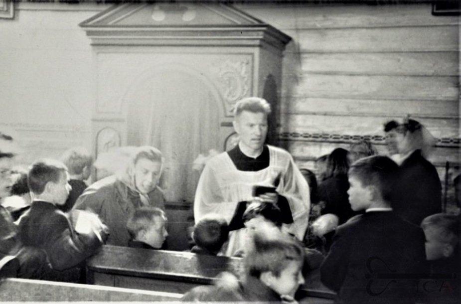 Kunigas Juozas Zdebskis su Pirmajai Komunijai ruošiamais vaikais Prienų Kristaus Apsireiškimo bažnyčioje. 1971 m. Fotonuotrauka. Lietuvos centrinis valstybės archyvas