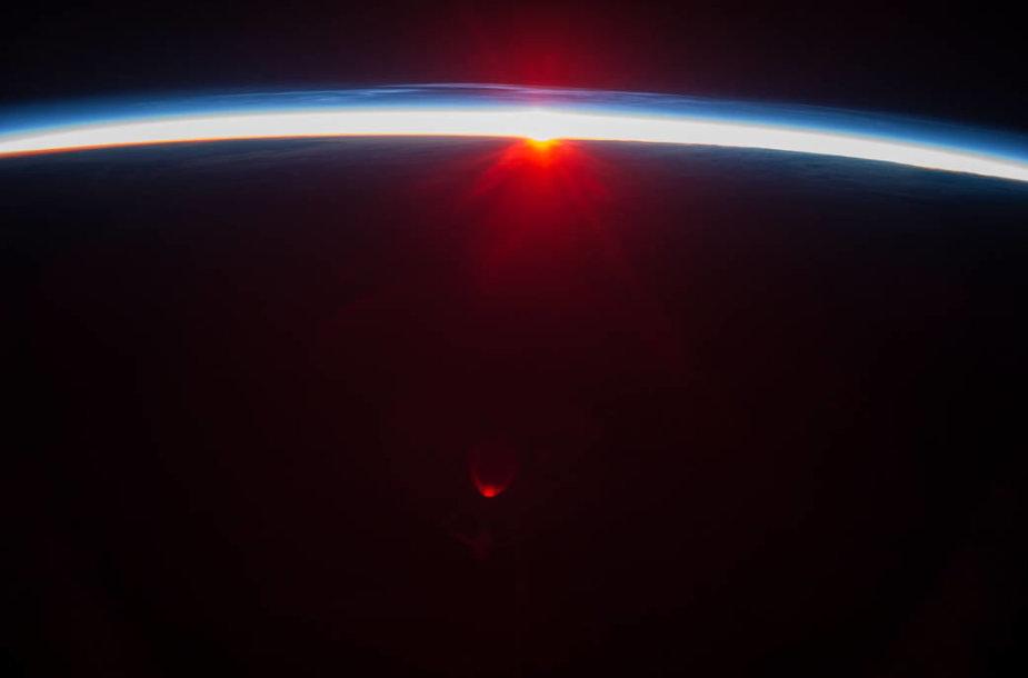 Šioje NASA nuotraukoje užfiksuotas saulėlydis virš Aleutų salų ir regima tankioji atmosferos sluoksnio dalis