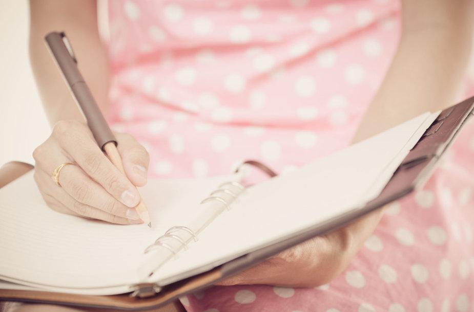 Mergina rašo dienoraštį.