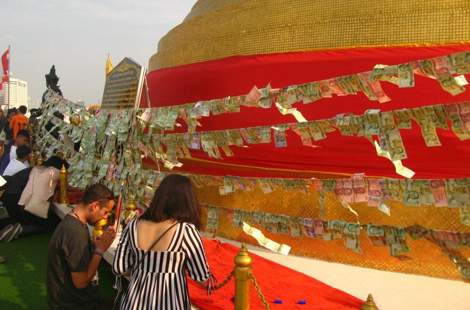 """Tradicinis aukojimo šventyklai būdas – banknotų kabinimas ant pinigų """"medžio""""."""