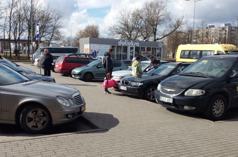 Kairėje – taksi automobilis, dešinėje – pavežėjo