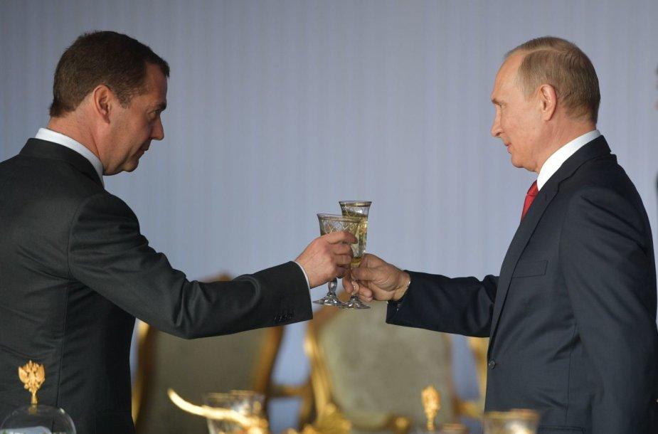 Vladimiras Putinas ir Dmitrijus Medvedevas susidaužia šampano taurėmis per šventinį priėmimą Maskvoje