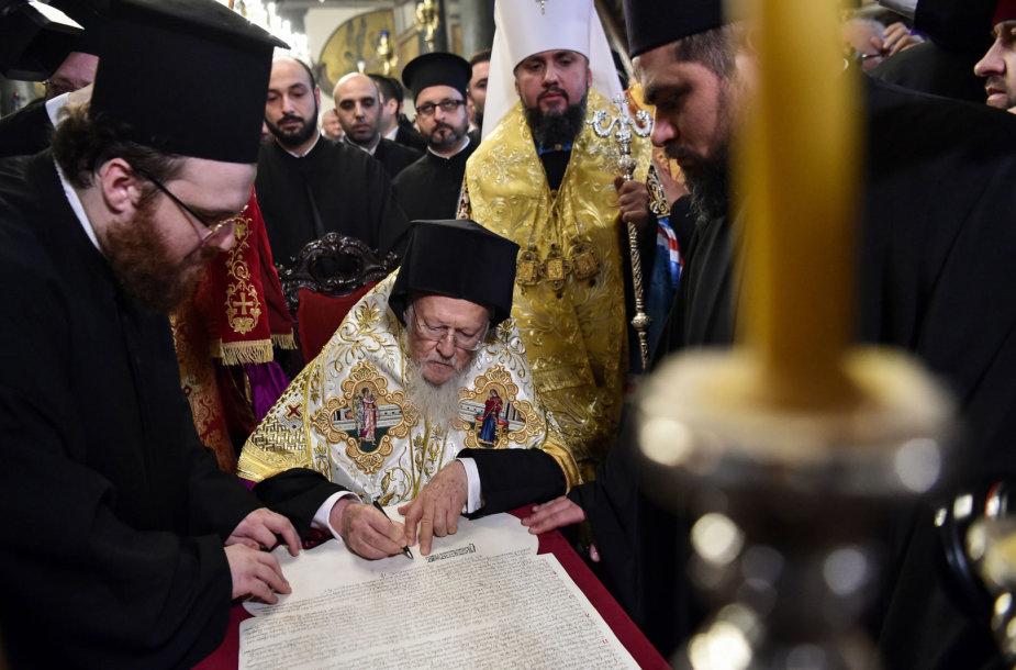 Konstantinopolio ekumeninis patriarchas Baltramiejus I pasirašo tomosą.