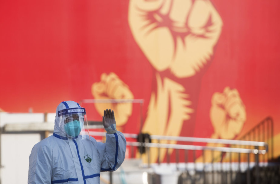 Medikas prie propagandinio plakato Kinijoje