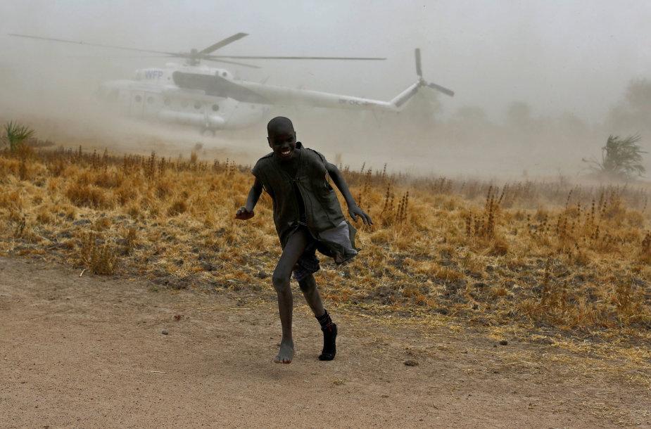Pietų Sudanas, 2017 vasario 18 d. Berniukas bėga nuo malunsparnio, atgabenusio maito paramą, sukeltų dulkių