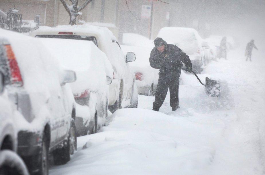 Čikagoje vyras prie savo automobilio kasa sniegą.