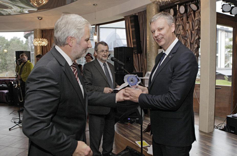 VRM Regioninės politikos departamento direktorius A.Plikšnys įteikė apdovanojimą Telšių rajono savivaldybės administracijos atstovui. VRM nuotr.