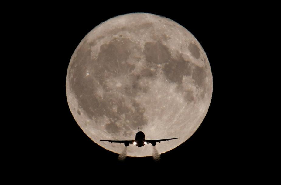 Londone kylantis lėktuvas mėnulio pilnaties fone