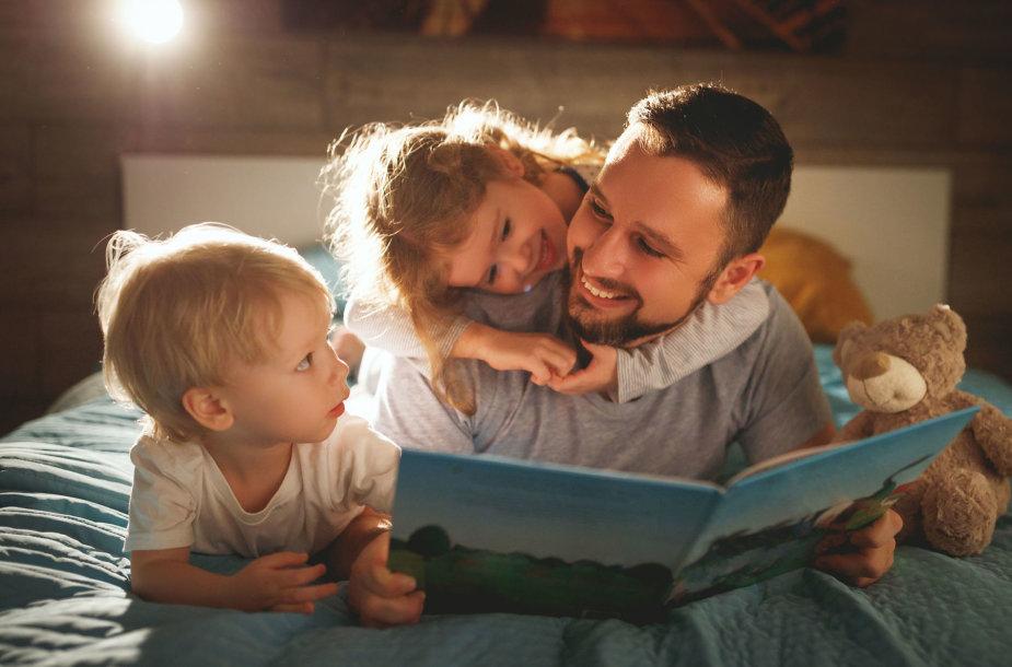 Tėtis vaikams skaito knygą