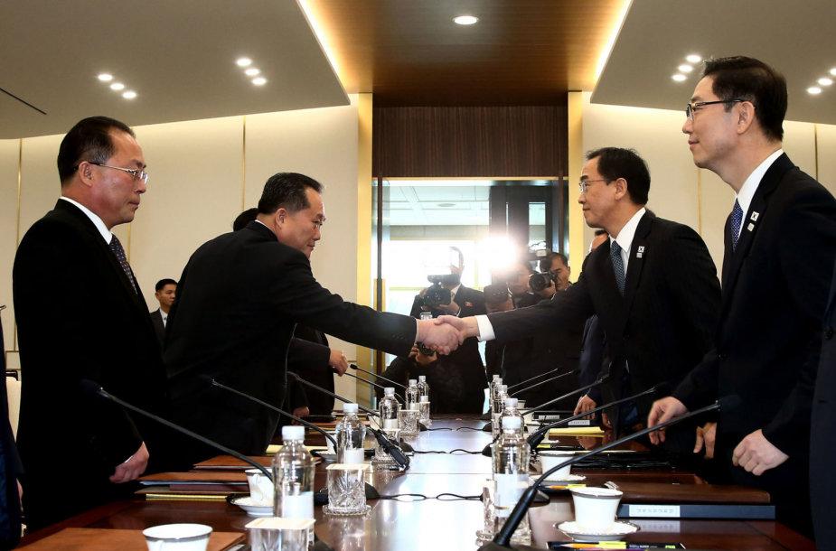 Sveikinasi Pietų Korėjos susivienijimo ministras Cho Myoung-gyonas (antras iš dešinės) ir Šiaurės Korėjos delegacijos vadovas Ri Son Gwonas (antras iš kairės)