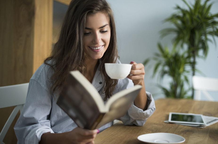 Mergina geria kavą ir skaito knygą
