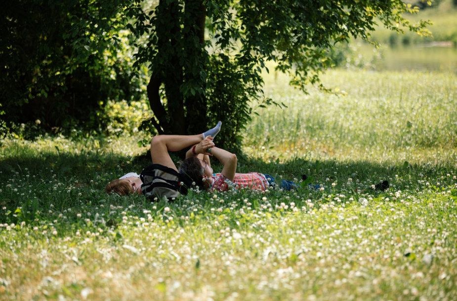 Žmonės guli žolėje