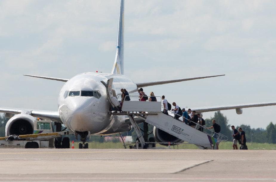 Žmonės lipa į lėktuvą