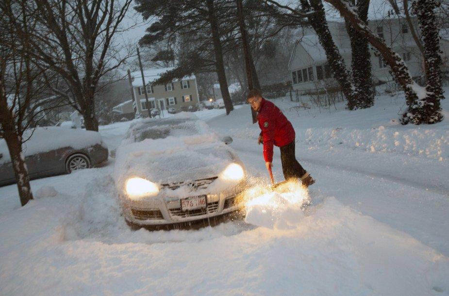 Vyras valo sniegą aplink savo automobilį.