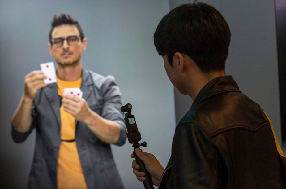 """Dešinėje – parodos CES lankytojas. Kairėje – ne žmogus, o skaitmeninis avataras """"Neon"""", kuris kažkada turėtų sugebėti bendrauti kaip žmogus"""