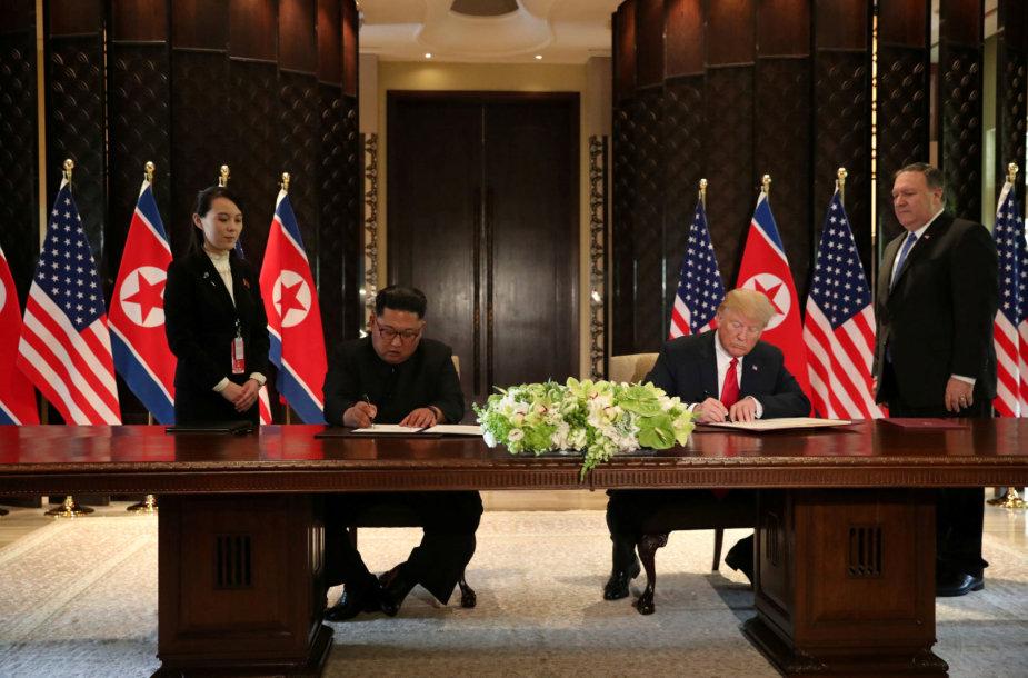Kim Jong Unas ir Donaldas Trumpas pasirašo dokumentą