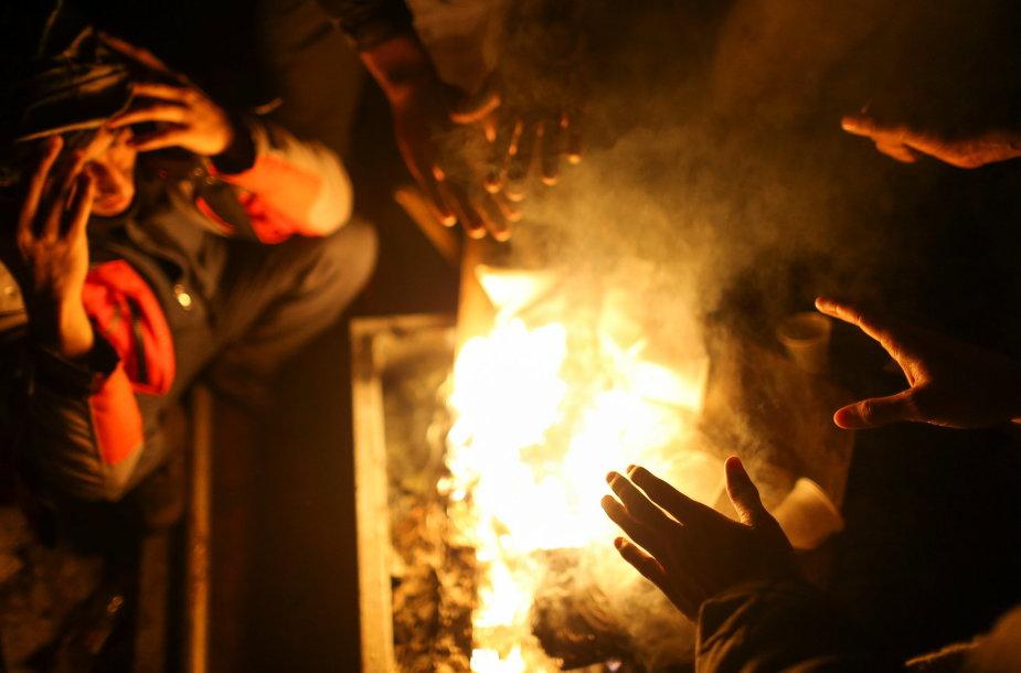 Migrantai šildosi prie atviros ugnies.