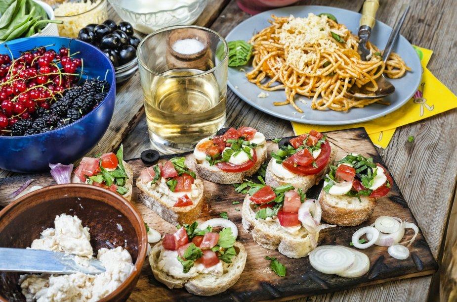 Itališkais valgiais ir užkandžiais nukrautas stalas