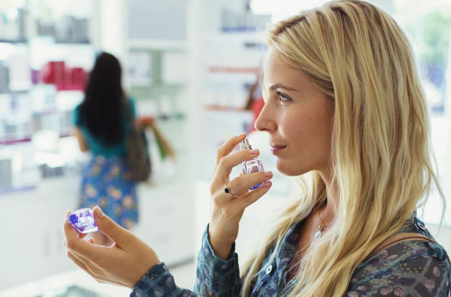 Moteris renkasi kvepalus parduotuvėje