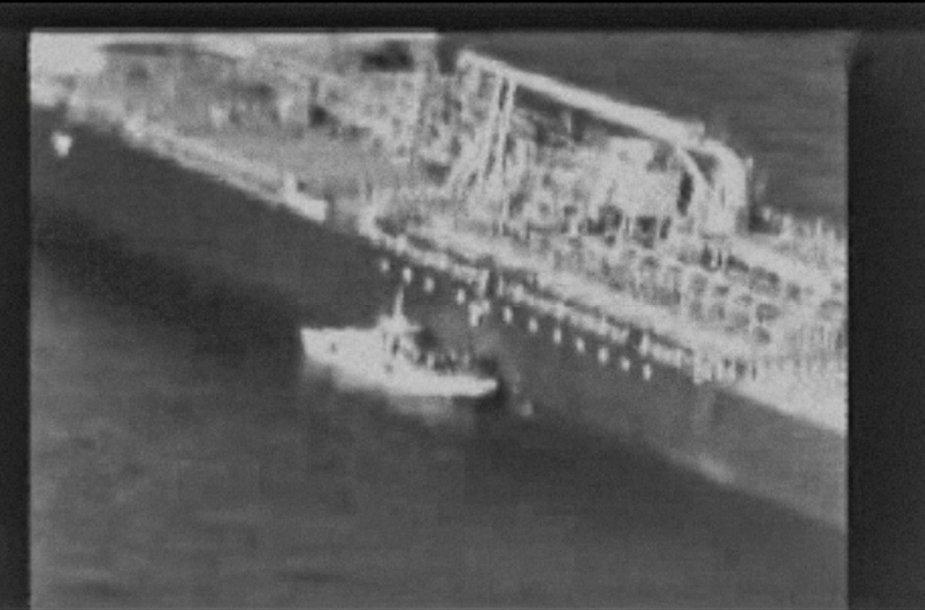 Kadras iš amerikiečių išplatinto vaizdo įrašo: iraniečiai nuplėšia miną nuo tanklaivio korpuso