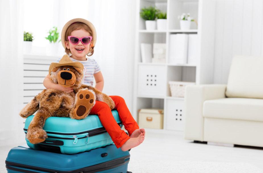 Laiminga mergaitė ant lagaminų