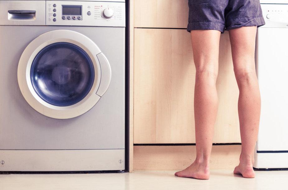 Moteris prie skalbimo mašinos