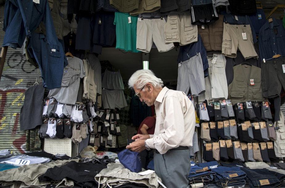 Vyriškis prie gatvėje įsikūrusios drabužių parduotuvės Atėnuose