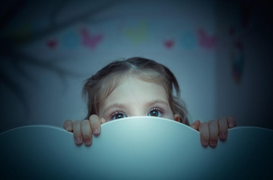 Mergaitė tamsoje.