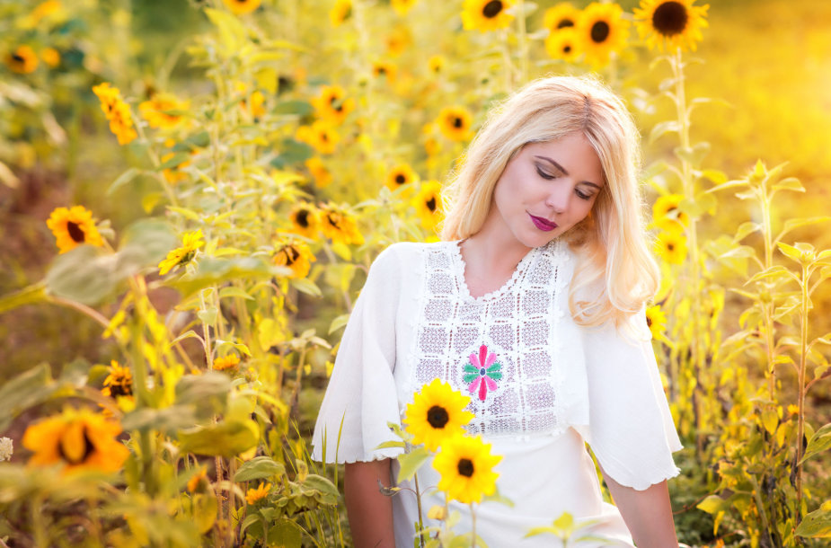 Moteris tarp gėlių