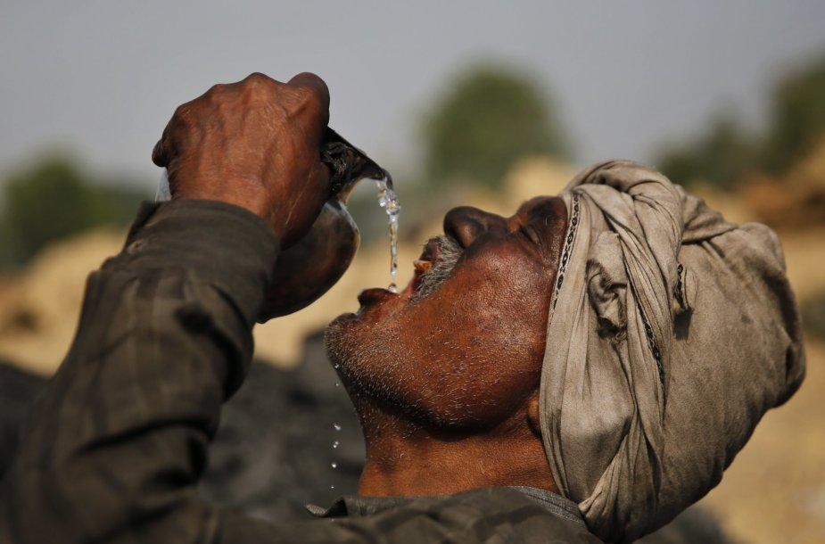 Darbininkas Indijoje geria vandenį