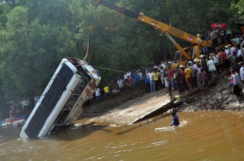 Gelbėtojai traukia autobusą iš upės.