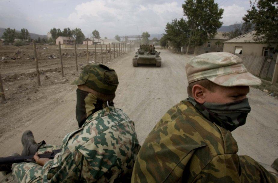 Rusų kariai važiuoja ant tanko viršaus