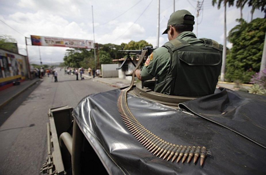 Venesuelos nacionalinės gvardijos karys pasienio poste nukreipęs ginklą į Kolumbijos pusę