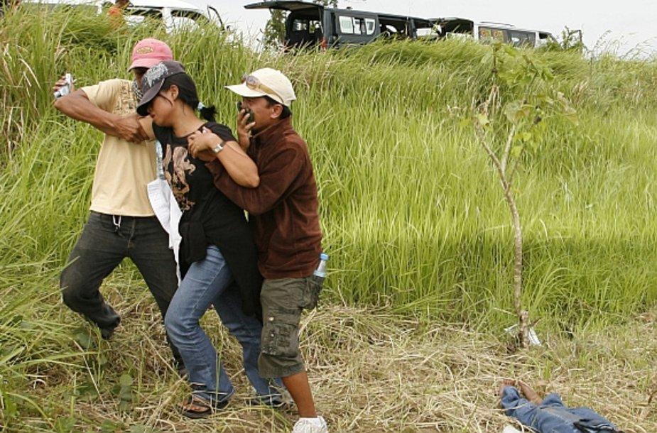 Vietinio nužudyto žurnalisto žmona nuvedama nuo vyro kūno.