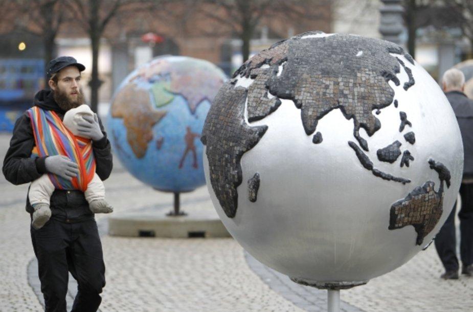 Vaiku nešinas Kopenhagos gyventojas eina pro gaublius, pastatytus miesto centre specialiai prieš konferenciją.