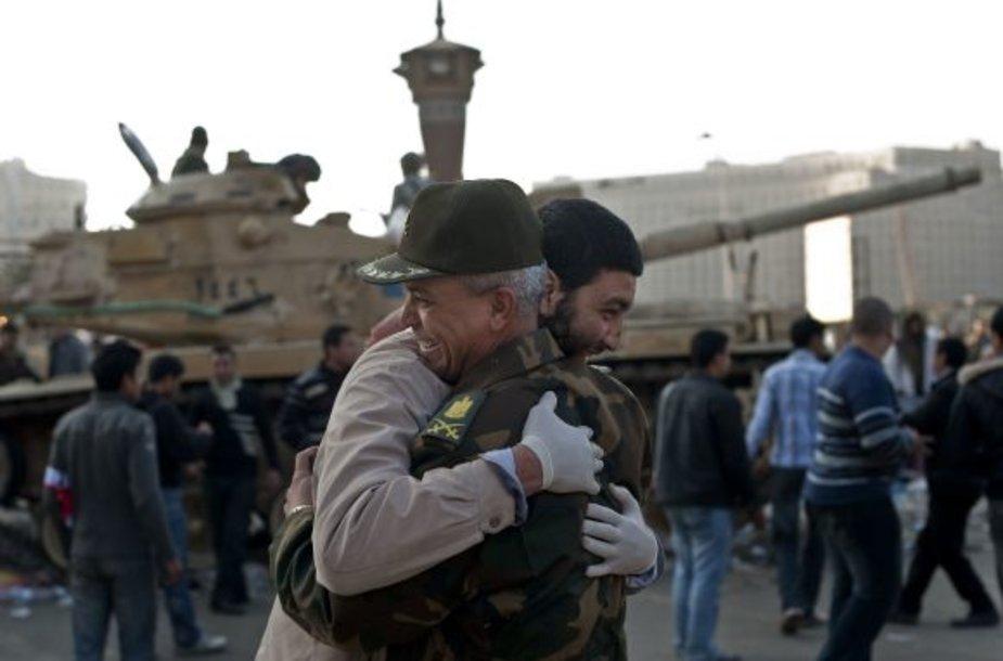 Civilis vyras ir karininkas Kaire glebėsčiuojasi sveikindami vienas kitą su revoliucijos pergale.