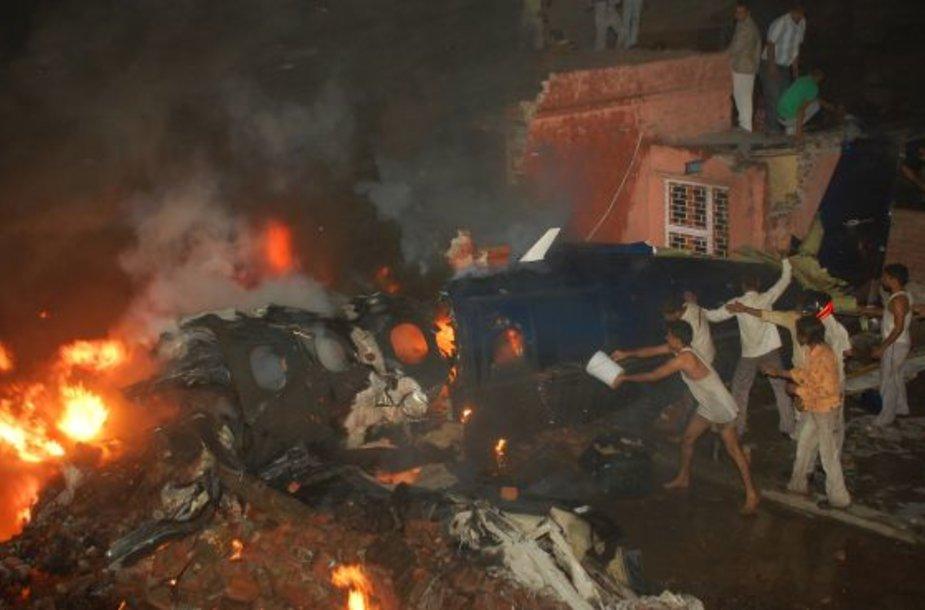 Vietos gyventojai mėgina užgesinti po aviakatastrofos įsiplieskusį gaisrą.
