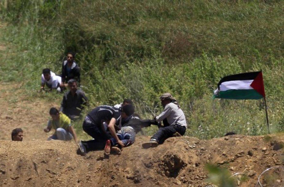 Palestiniečiai protestuotojai velka sužeistą draugą.